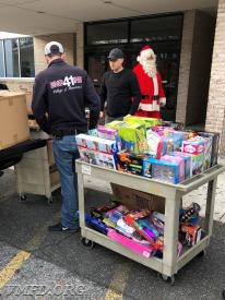 Santa Clause and his Elf's unloading the toys